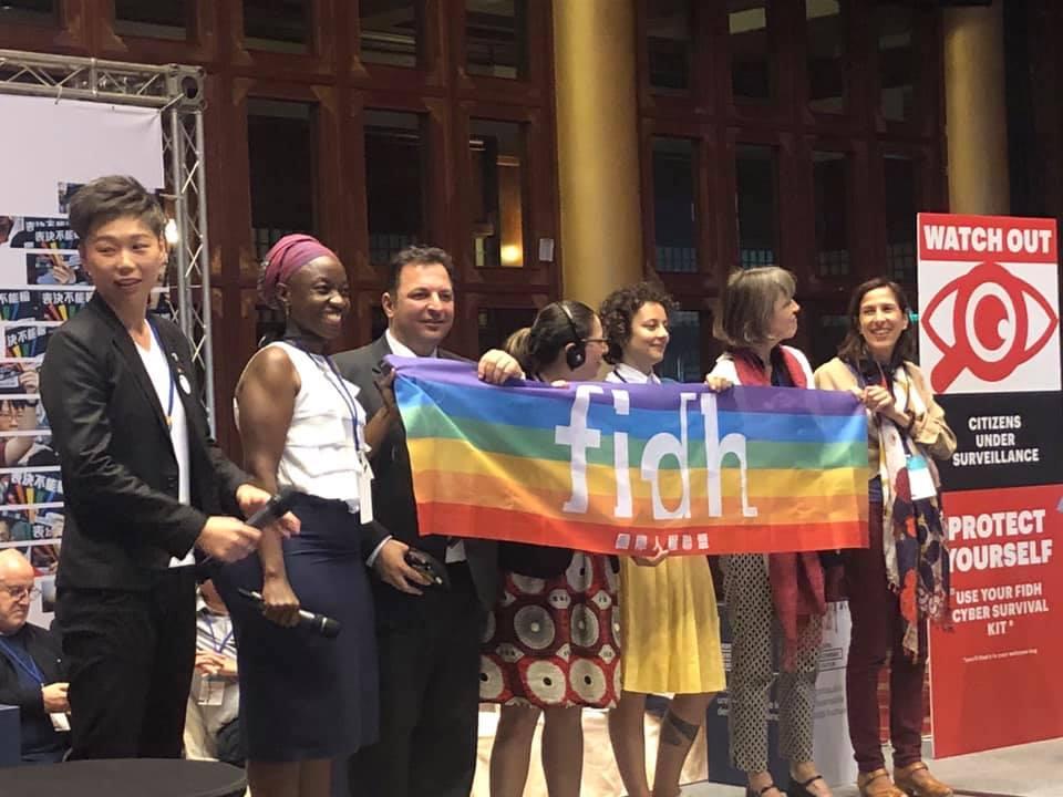 Panelisté závěrečné diskuse s vlajkou FIDH